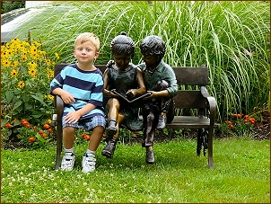 Children Statues boy and girl on bench cast in bronze
